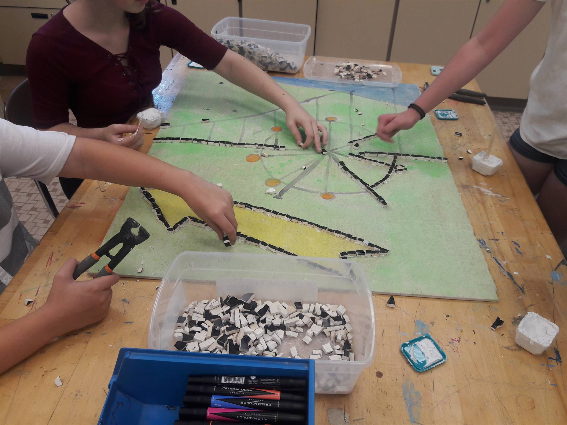 Students are outlining the Mosiac with black tile