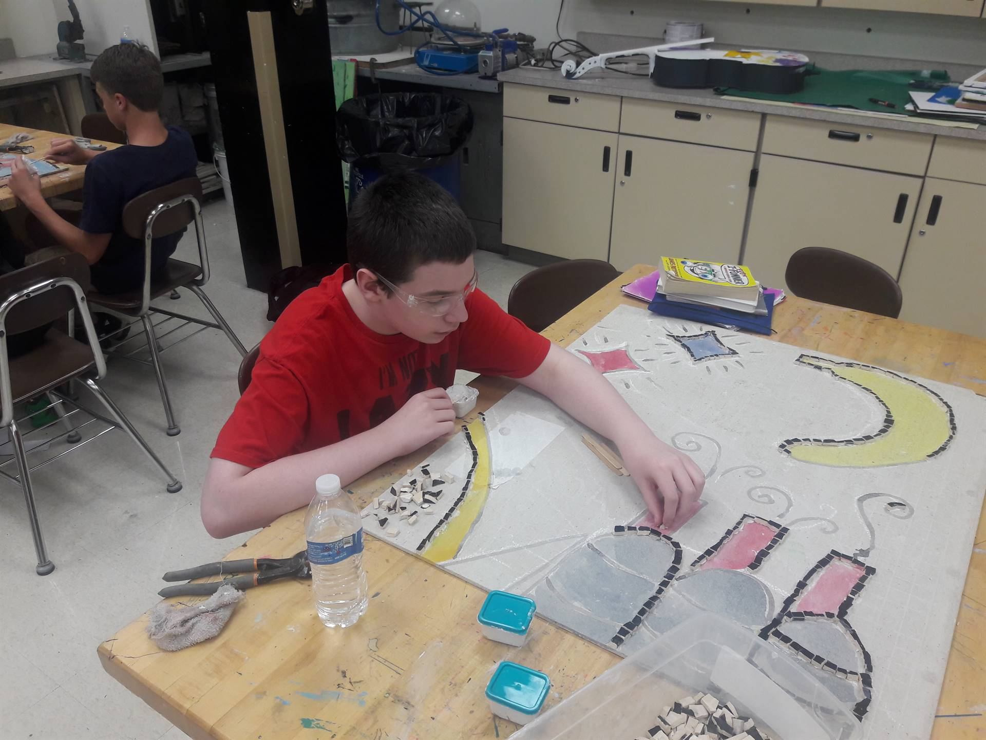 Students are outlining the Mosaic with black tile
